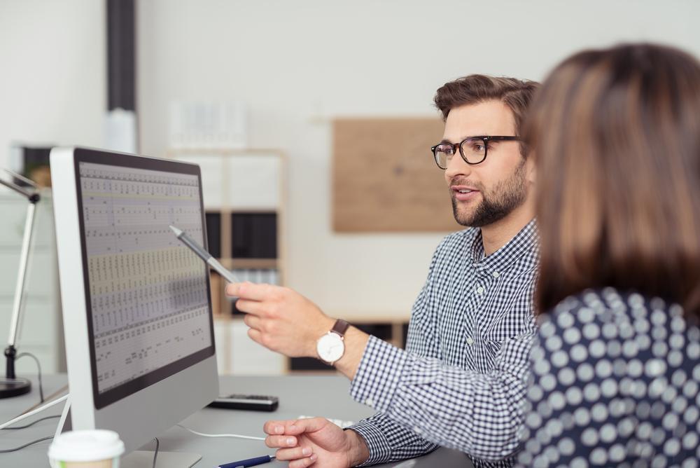 パソコンの画面を見ながら教える男性