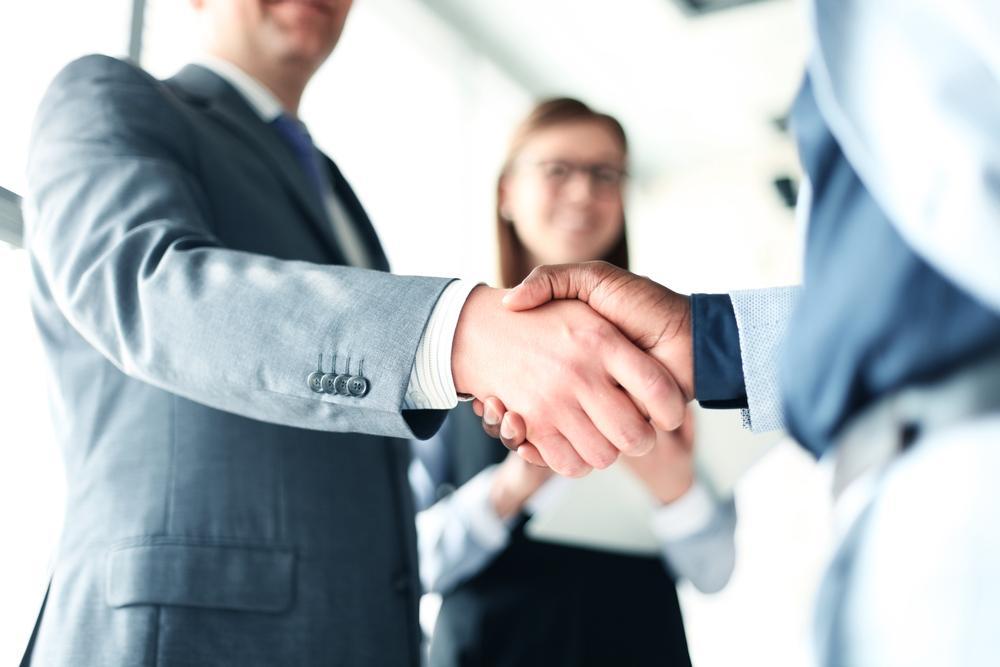 握手を交わすビジネスパーソンたち