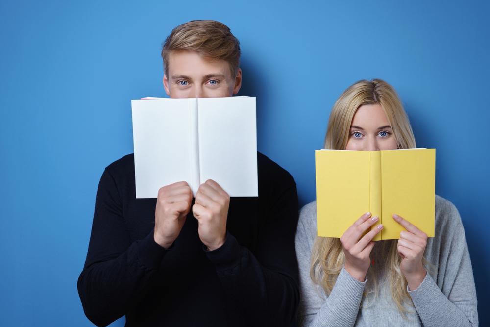 本で顔を隠している男女