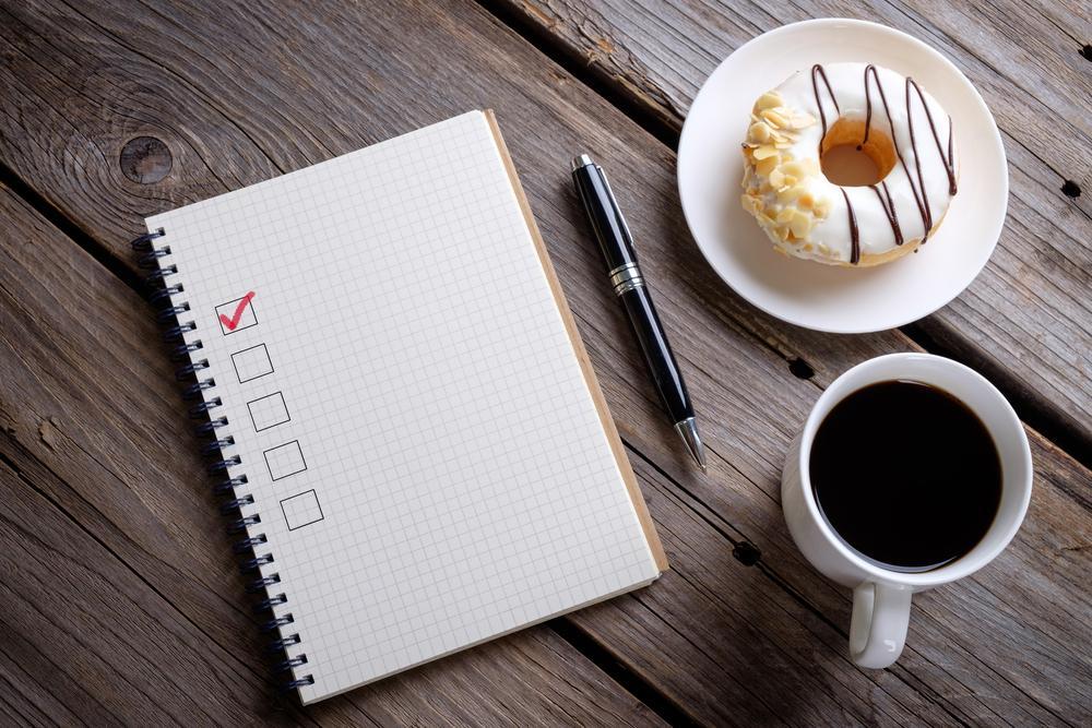 机の上に置かれたメモ帳とドーナツとコーヒー