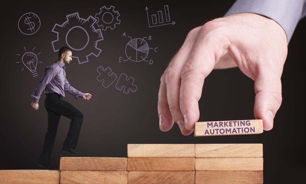 階段を進むビジネスマンとマーケティングオートメーションのブロックを積み上げる手
