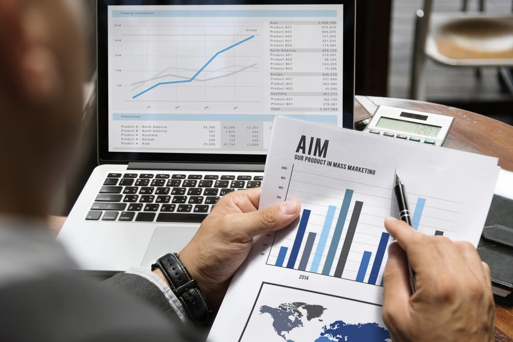 資料のグラフとパソコンのグラフを突き合わせるビジネスマン