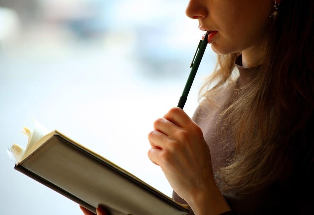 手帳を見ながら悩む女性