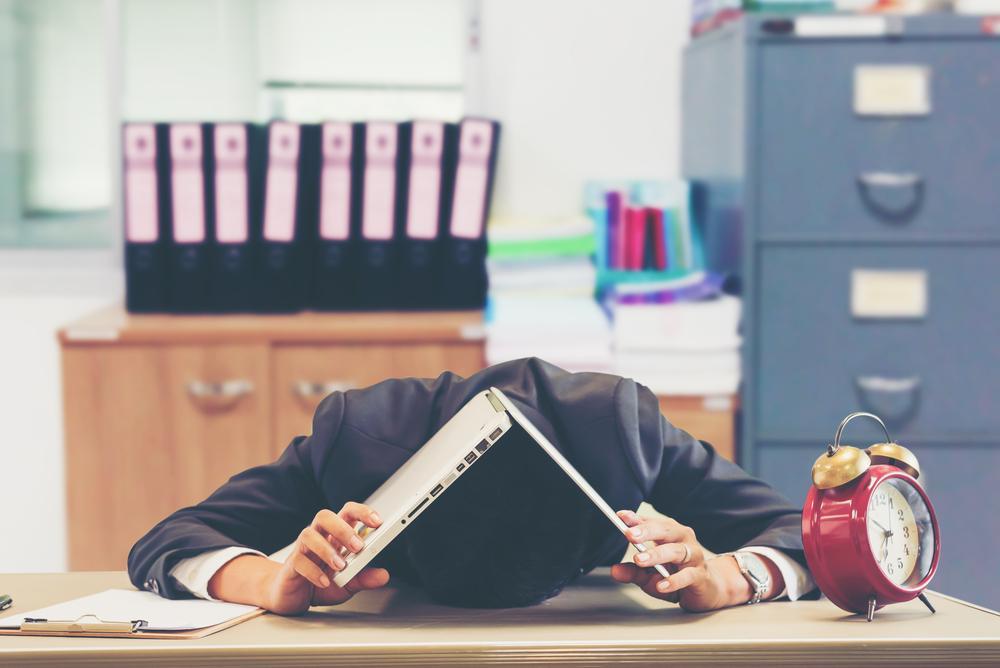 パソコンを被り伏せるビジネスマン