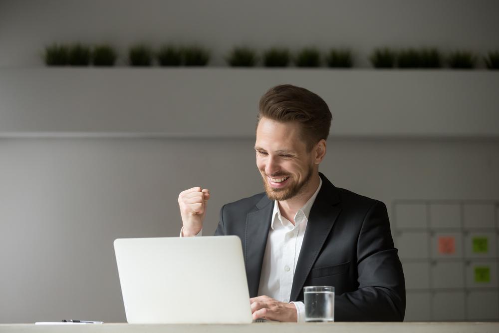 パソコンの前でガッツポーズをするビジネスマン